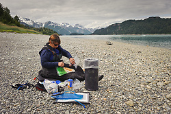 A kayaker prepares lunch on a Wachusett Inlet beach just off Muir Inlet in Glacier Bay National Park and preserve in southeast Alaska. Also pictured is a bear resistant food container. Use of a bear resistant food container is required by the park as a way to control conflicts with black and grizzly bears. Kayakers are advised to eat in the intertidal zone so any dropped food particles are washed away during high tide.