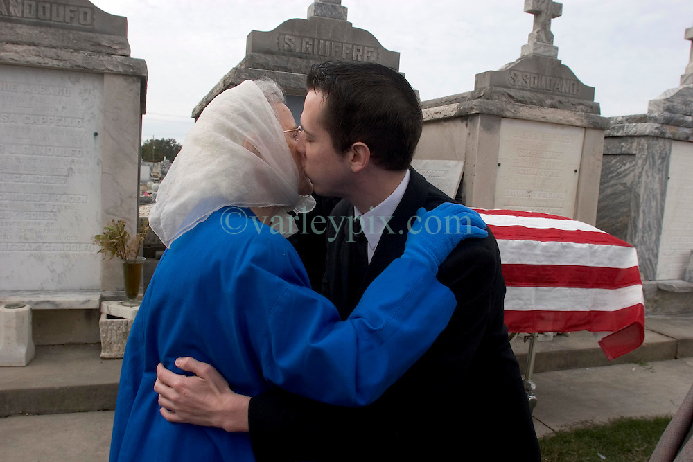 09December 05.  New Orleans, Louisiana. Hurricane Katrina Aftermath. <br /> 3 1/2 months after the storm, New Orleans continues to bury the victims. 77 year old widow Geneva is embraced by her grandson at the funeral of her husband Vincent Giuffre at Greenwood cemetery. 87 year old Guiffre died in the arms of his 77 yr old wife Geneva in New Orleans East as the flood waters swirled around their kitchen. Geneva placed her cat Patsy in her attic, fully expecting her beloved pet to die. She swam out of her back door, leaving her husband's body floating in the kitchen. She held onto the drain surrounding her house roof and made her way to the front of the building where she clung on to the drainpipe for 3 days. Geneva was rescued by helicopter, taken to Houston. Her frantic family did not learn that she was safe for 4 days. The only thing she was able to save from her house was her wedding ring. Geneva and Vincent had been married 56 years. Miraculously a neighbour saved her cat, discovering it alive 3 weeks after the storm hit. Geneva and her cat now live with her son Gary in Atlanta.<br /> Photo; ©Charlie Varley/varleypix.com