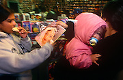 A young child is in a Bollywood music shop with its mother near a movie magazine reader in Southall.
