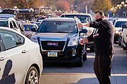 06 NOVEMBER 2020 - DES MOINES, IOWA: MARK ENDERSON, a volunteer, directs traffic during a drive through emergency food distribution at the Iowa State Fairgrounds Friday. A spokesperson for the Food Bank of Iowa said they had enough food for 1,500 families. Each family got frozen chicken legs, frozen liquid eggs, and fresh produce. There will be another emergency food distribution at the Fairgrounds on November 30. Food insecurity in the Des Moines area has skyrocketed since the start of the Coronavirus pandemic. Although unemployment rates in Iowa have fallen since a peak in June, many families that fell behind on rent are now facing eviction. The food bank spokesperson said use of the Food Bank's emergency pantries and distribution points is still increasing.    PHOTO BY JACK KURTZ