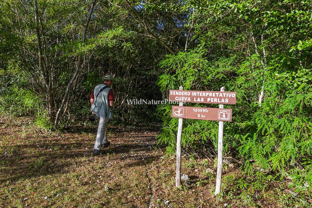 A birder enters a trail in La Bejada, Guanahacabibes National Park, Cuba.