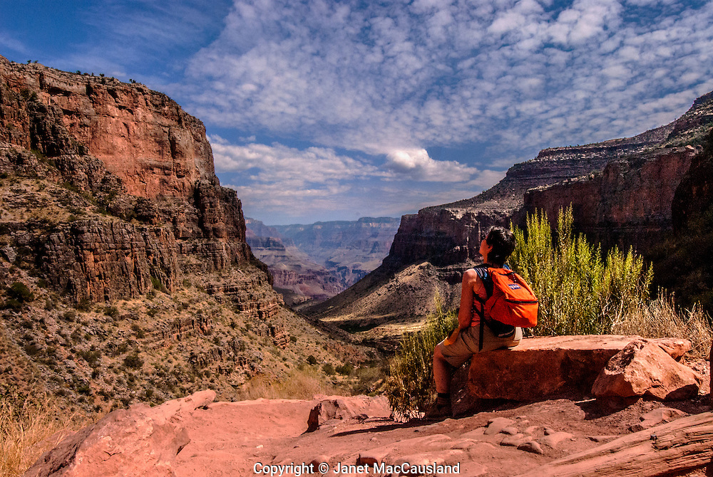 A woman rests while looking up to where we came, along the Bright Angel Trail in the Grand Canyon, Arizona. The Canyon is over a mile deep.