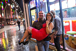 © Licensed to London News Pictures . 21/12/2013 . Manchester , UK . A man carries a woman outside a takeaway . Christmas revellers out in the rain in Manchester on Mad Friday , the last Friday night before Christmas which is typically one of the busiest nights of the year for police and ambulance crews . Photo credit : Joel Goodman/LNP