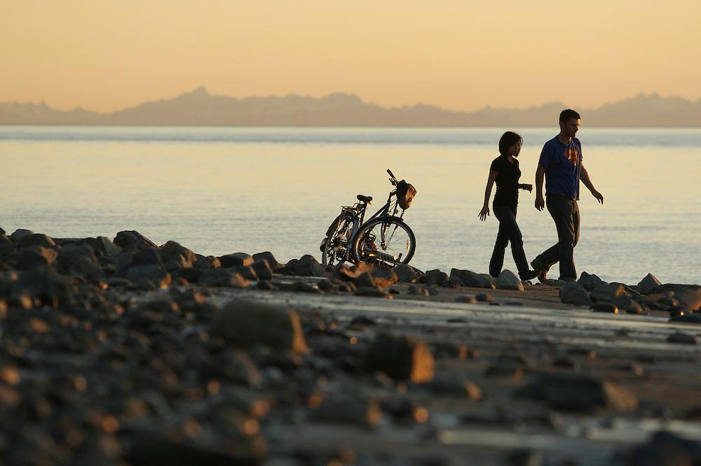 Couple on beach at sunset near Point Woronzof, Anchorage, Alaska