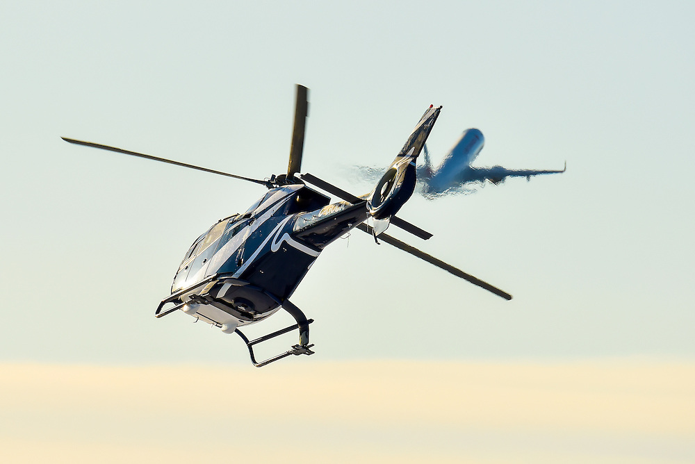 A helicopter takes off as a commercial jet climbs away