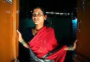 """Kasvva Haragan, 28, waits for a customer at her brothel door in Gokak, India.  Her  parents dedicated her as a Devadasi at the age 12 and to avoid the legal ramifications of the Devadasi Protection Act, had a ceremony at home. She now lives and works in a brothel with 2 other women and support her parents, two sisters and a brother.  She also gives 50% of her earnings to the brothel owner. """"Who would want to marry me? I'm a Devadasi,"""" she says when asked if she'd like to marry a man. Haragan is illiterate as she worked in the sugar cane fields as a child rather than going to school and therefore has few other options to make an income. ."""