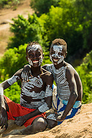 Kara tribe boys with body chalk paintings on their bodies. The Omo River is behind. Dus village, Omo Valley, Ethiopia. Omo Valley, Ethiopia.