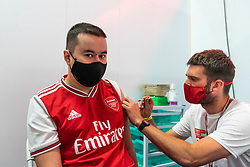 """© Licensed to London News Pictures. 25/06/2021. LONDON, UK.  Gunners fan Lorenzo Homa, aged 22, receives a first dose of the Pfizer vaccine at a pop-up mass vaccination clinic Arsenal's Emirates Stadium as part of a """"Gunner Get Jabbed"""" event organised by Islington Council, the local GP federation and the football club.  The NHS is also promoting a number of walk-in clinics this weekend across the capital to try to increase the number of over 18s receiving a jab as cases of the Delta variant are reported to be on the rise.  Photo credit: Stephen Chung/LNP"""