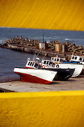 Magdalen Islands, New Brunswick: Yellow bridge trusses frame fishing boats pulled up on the docks at Point Old-Harry, making a colorful statement typical of the Canadian Maritimes..