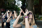 Three female photographers taking pictures at the same time together in London, United Kingdom.