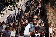 Woman passes below a billboard for clothing retailer Tommy Hilfiger showing the wealthy classes in a country setting.