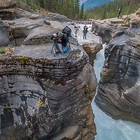 Banff National Park, Alberta, Canada. Photographers frame views of Mistaya Canyon, where the large Mistaya River plunges into a narrow slot canyon it has eroded over time. Behind is Mount Sarbach.