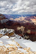 A winter storm starts to clear over the Grand Canyon as sunlight dances upon the canyon wall.