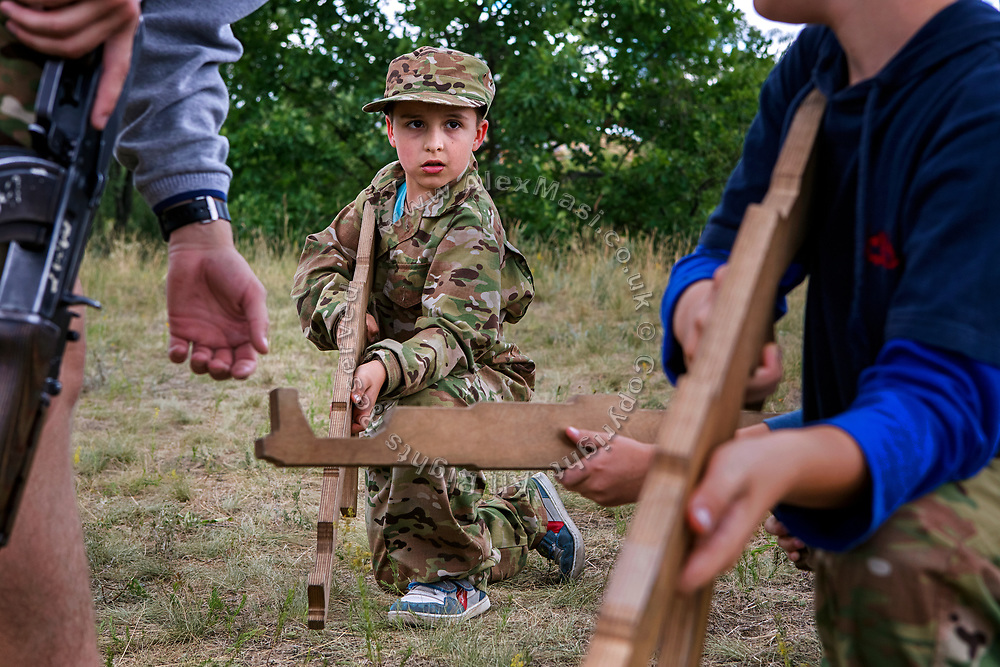 Youngsters participating to the ultra-nationalistic Azovets children's camp are holding wooden rifles and being taught combat positions by their instructor, during tactical training , on the banks of the Dnieper river in Kiev, Ukraine's capital.