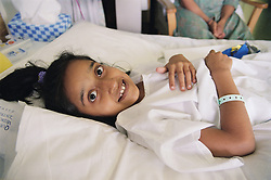 Young girl with spinal disease lying on hospital bed on Spinal ward smiling,