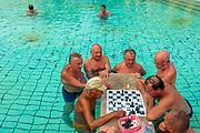 A group of elderly men watch a games of chess played whilst imersed in the Széchenyi Medicinal Bath, Budapest, Hungary