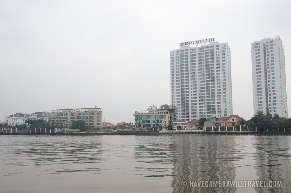 Modern residential buildings tower above the banks of the Saigon River in Ho Chi Minh City, Vietnam.