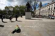 A young boy draws on the pavement below a statue of Winston Churchill and opposite The Houses of Parliament during a May Day demonstration in Parliament Sqaure, London.