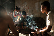 In this Sept. 16, 2017 photo, Jayanne Pessanha, right, smokes a cigarette while playing cards with neighbors in a squatter building that used to house the Brazilian Institute of Geography and Statistics (IBGE) in the Mangueira slum of Rio de Janeiro, Brazil. Pessanha, 20, said her sister died a few years ago after falling from an empty window, and her brother died when he hit his head during a fight.(AP Photo/Felipe Dana)