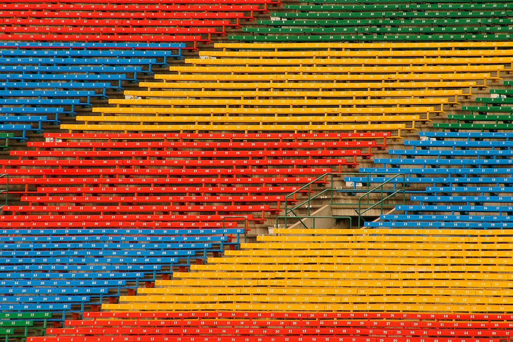 Signed, limited edition fine art photograph depicting red, yellow, blue, and green bleachers on the east side stands, Taylor Field at Mosaic Stadium, Regina Saskatchewan, home of the Saskatchewan Roughriders