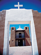 An old archway creates an entrance to an adobe church in the desert of New Mexico