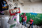 "Children carry their shopping up the crumbling concete stairs at the high-rise building ""Hrebenova 34-36"" which was in appalling condition and demolished in August 2014 by the city of Kosice. The Lunik IX estate is almost entirely populated by Roma and living conditions for the residents are appalling, many people do not have electricity, water or gas. 95 percent of former residents had no rental contract and thus no right for a compensatory flat. A new shanty village, populated by such families, is growing beside Lunik IX"