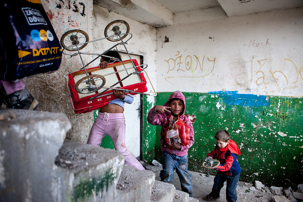"""Children carry their shopping up the crumbling concete stairs at the high-rise building """"Hrebenova 34-36"""" which was in appalling condition and demolished in August 2014 by the city of Kosice. The Lunik IX estate is almost entirely populated by Roma and living conditions for the residents are appalling, many people do not have electricity, water or gas. 95 percent of former residents had no rental contract and thus no right for a compensatory flat. A new shanty village, populated by such families, is growing beside Lunik IX"""