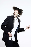 studio shot portrait of a young funny expressive thin and tall man on isolated background listenning music to a mp3 type player beeing an Air guitar hero pretending to play