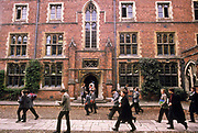 Students walking to lessons inside the private and exclusive Winchester College one of the country's top schools, Winchester city, UK