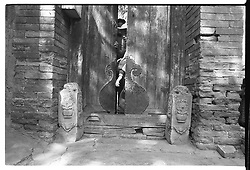 Children looking out form behind old door in house in hutong in Bejing