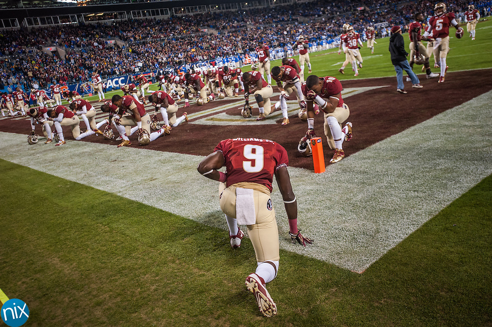Florida State's Karlos Williams (9) and other players pray prior to taking on Duke during the ACC Championship game at Bank of America Stadium in Charlotte Saturday night. Florida State won the game 45-7.