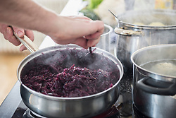 Chef cooking red cabbage on stove