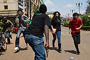 An armed security officer (C) assists civilians escaping from the Westgate Shopping Centre.
