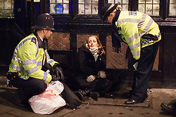 © licensed to London News Pictures. London, UK 14/12/2013. Police officers helping an unwell woman in Soho, London on the last Friday night before Christmas, which is also the busiest night of the year for emergency services. Photo credit: Tolga Akmen/LNP