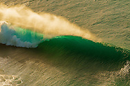 Aerial view of a the golden spray coming off of a backlit wave breaking off the Na Pali coast of Kauai, Hawaii