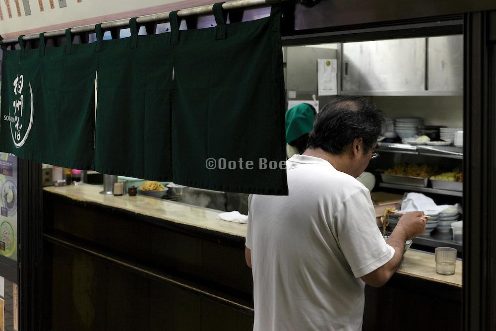 man eating standing at a Japanese noodle restaurant shops