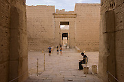Guards and a few tourists near Ramessid columns in the peristyle court at the ancient Egyptian site of Medinet Habu (1194-1163BC), the Mortuary Temple of Ramesses III in Luxor, Nile Valley, Egypt. Medinet Habu is an important New Kingdom period structure in the West Bank of Luxor in Egypt. Aside from its size and architectural and artistic importance, the temple is probably best known as the source of inscribed reliefs depicting the advent and defeat of the Sea Peoples during the reign of Ramesses III.
