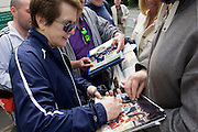 Day 2 of the annual lawn tennis championships and former champion Billie Jean King signs autographs for souvenir hunters at a side entrance of the venue. Billie Jean King is an American former World No. 1 professional tennis player. King won 39 Grand Slam titles, including 12 singles, 16 women's doubles, and 11 mixed doubles titles and winning a record 20 career titles at Wimbledon - six singles, ten women's doubles, and four mixed doubles. The Wimbledon Championships, the oldest tennis tournament in the world, have been held at the nearby All England Club since 1877.