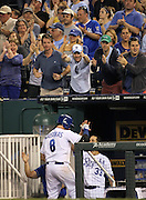 Kansas City Royals fans cheer on batter, Mike Moustakas (8) after hitting a sacrifice fly ball to score one run during the 7th inning of their baseball game against the Tampa Bay Rays at Kauffman Stadium in Kansas City, Mo., Tuesday, April 30, 2013.  (AP Photo/Colin E. Braley).