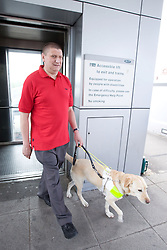 Vision impaired man and guide dog coming out of a lift together,