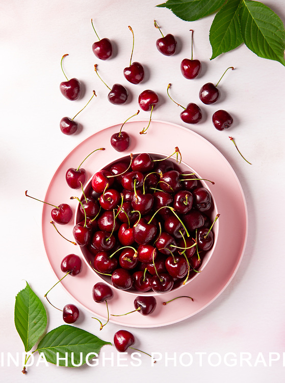Bowl of cherries on a pink marbled surface