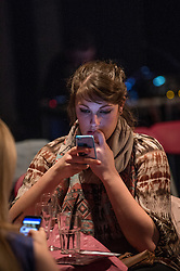Young people using mobile phones in cafe UK