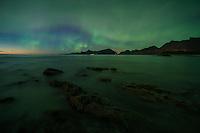 Northern lights fill sky over coastal mountains from Ytresand beach, Moskenesøy, Lofoten Islands, Norway