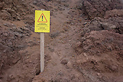 Tourists' warning sign embedded in lava rock at the dormant crater edge of Vesuvius volcano. Telling visitors not to climb over fences and endanger their lives, the sign shows an exclamation mark. Mount Vesuvius is best known for its eruption in AD 79 that led to the burying and destruction of the Roman cities of Pompeii and Herculaneum. That eruption ejected a cloud of stones, ash and fumes to a height of 33 km (20.5 mi), spewing molten rock and pulverized pumice at the rate of 1.5 million tons per second. From the chapter entitled 'Under the Volcano' and from the book 'Risk Wise: Nine Everyday Adventures' by Polly Morland (Allianz, The School of Life, Profile Books, 2015).