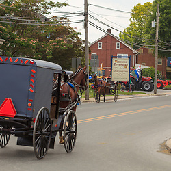 Intercourse, PA - June 17, 2012: Horse-drawn Amish buggies  travels on a village road in Lancaster County.