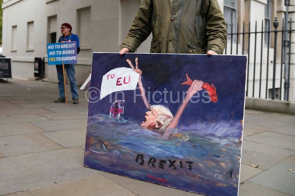 Satirical artist Kaya Mar with his latest take on the government, outside the Houses of Parliament on 23rd October, 2019 in London, England, United Kingdom. The government await news from the EU granting another Brexit extension. Last night Prime Minister Boris Johnson 'paused' discussions on his EU withdrawal bill after MPs voted against the government rushing it through in three days, Speaker John Bercow described the bill as bill now being in limbo.