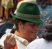A woman with green felt hat and gold necklace attends Otavalo Market in Ecuador, Imbabura Province, South America. The culturally vibrant town of Otavalo attracts many tourists to a valley of the Imbabura Province of Ecuador, surrounded by the peaks of Imbabura 4,610m, Cotacachi 4,995m, and Mojanda volcanoes. The indigenous Otavaleños are famous for weaving textiles, usually made of wool, which are sold at the famous Saturday market and smaller markets during the rest of the week. The Plaza del Ponchos and many shops tantalize buyers with a wide array of handicrafts. Nearby villages and towns are also famous for particular crafts: Cotacachi, the center of Ecuador's leather industry, is known for its polished calf skins; and San Antonio specializes in wood carving of statues, picture frames and furniture. Otavaliña women traditionally wear distinctive white embroidered blouses, with flared lace sleeves, and black or dark over skirts, with cream or white under skirts. Long hair is tied back with a 3cm band of woven multi colored material, often matching the band which is wound several times around their waists. They usually have many strings of gold beads around their necks, and matching tightly wound long strings of coral beads around each wrist. Men wear white trousers, and dark blue ponchos. Otavalo is also known for its Inca-influenced traditional music (sometimes known as Andean New Age) and musicians who travel around the world.