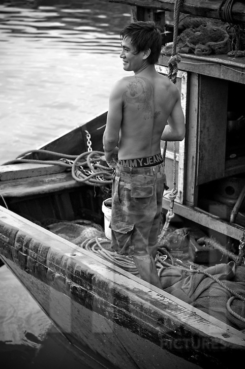 A young barechested vietnamese fisherman stands on his boat and laughs. He's got a dragon tattoo on his back. Khanh Hoa area, Vietnam, Asia