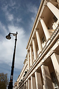 A vertical version that shows the Corinthian columns and covered doorways of exclusive and classically-designed properties in London's famous Eaton Square Belgravia, SW1, owned by Grosvenor Estate. It is a bright spring day with a blue city sky and high, thin clouds. The sun shines on the cream-coloured architectural features and some shadows from trees opposite can be seen on the lower upright pillars and an ornate lamp post. Eaton Square is one of London's three garden squares built by Thomas Cubitt and the Grosvenor family when they developed the main part of Belgravia from 1826 until 1855. Belgravia attracts actors, politicians, ambassadors, big-budget bankers, traders and Prime Ministers like Neville Chamberlain and Stanley Baldwin at number 93.