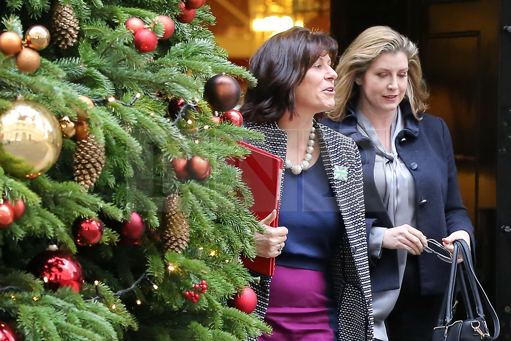 """© Licensed to London News Pictures. 18/12/2018. London, UK. Claire Perry - Minister of State at Department for Business Energy and Industrial Strategy (L) and Penny Mordaunt - Secretary of State for International Development and Equalities Minister (R) departs from No 10 Downing Street after attending the weekly Cabinet Meeting that discussed the preparations for a """"No Deal"""" Brexit. Photo credit: Dinendra Haria/LNP"""